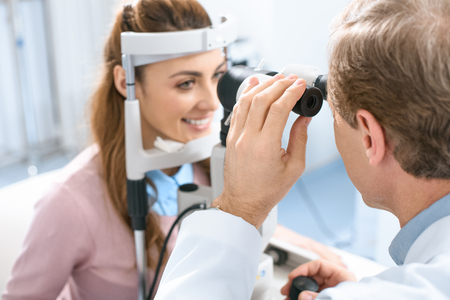 oculist examining patient vision with slit lamp in clinic Stok Fotoğraf