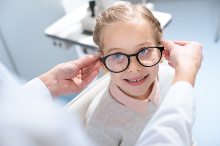 oculist and little child in glasses in optical clinic Stock Photo - 111696105