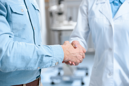 partial view of man shaking hands with doctor in clinic