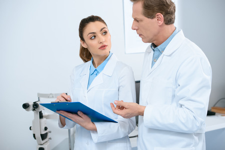 male and female ophthalmologists writing diagnosis in clinic Stock Photo