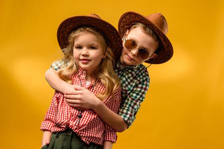 kleine stijlvolle cowboy en cowgirl in hoeden knuffelen geïsoleerd op geel