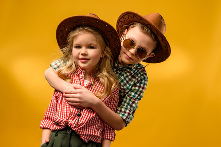 little stylish cowboy and cowgirl in hats hugging isolated on yellow Stockfoto
