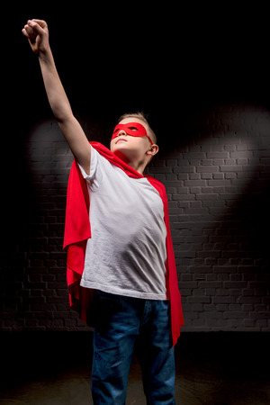 boy flying in superhero costume and red mask