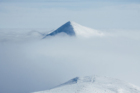 Mountain peak over clouds in winter