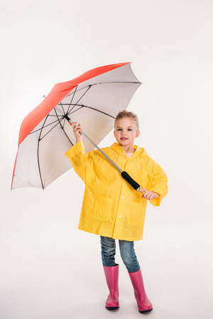 preschooler child in rubber boots, yellow raincoat with umbrella, isolated on white