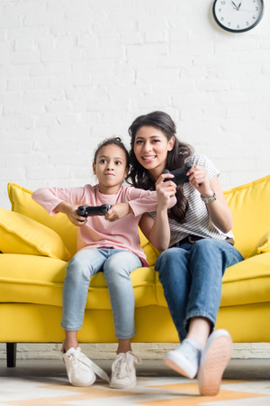 happy young mother and daughter playing video games at home on couch