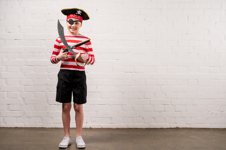 little smiling boy with toy knife and gun in pirate costume