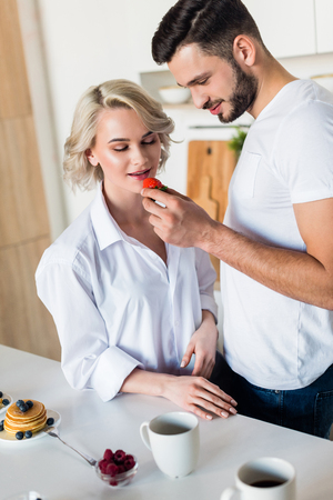 smiling young man feeding sexy girlfriend with strawberry at morning Stock Photo