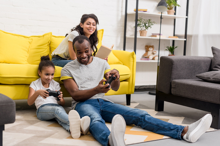 Happy father and daughter playing video games while mother sitting on couch Stok Fotoğraf