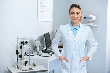 Smiling female optometrist posing in optical clinic