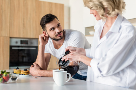 Young woman pouring coffee and looking at handsome boyfriend at morning in kitchen Imagens