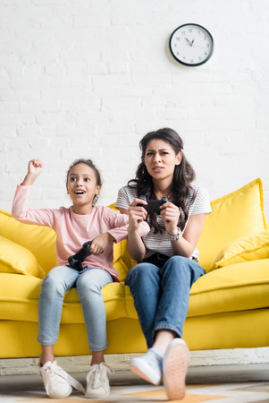 Emotional mother and daughter playing video games at home on couch Stok Fotoğraf