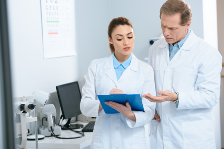 Male and female optometrists writing diagnosis in optical clinic