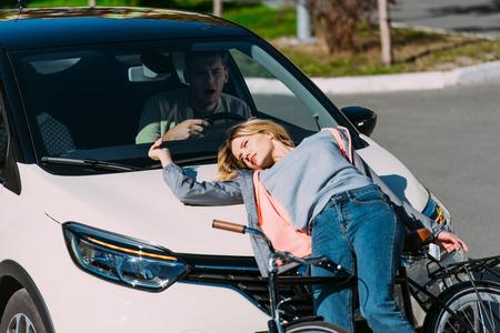 Mujer joven ir atropellada por coche mientras conduce bicicleta en la carretera, concepto de accidente de coche