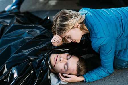 Young woman crying and looking at dead man on road