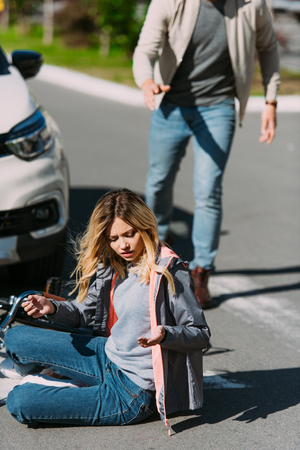 Selective focus of injured woman on road after car accident with car driver behind Stok Fotoğraf