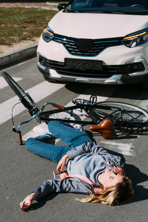 Young woman go mowed down by car while driving bicycle on road, car accident concept