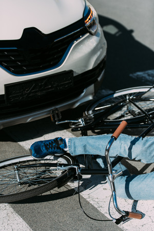 Partial view of male bicycle rider hit by car on road, car accident concept 스톡 콘텐츠
