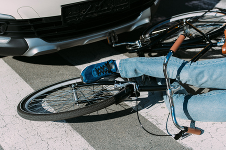 Partial view of male bicycle rider hit by car on road, car accident concept 写真素材