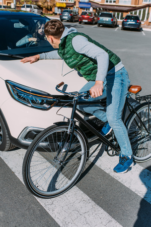 Male bicycle rider hit by woman in car on road, car accident concept 写真素材 - 112271210