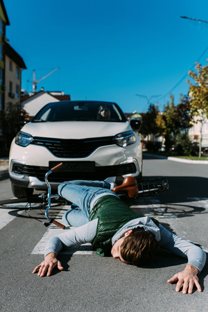 Male bicycle rider hit by woman in car on road, car accident concept 스톡 콘텐츠