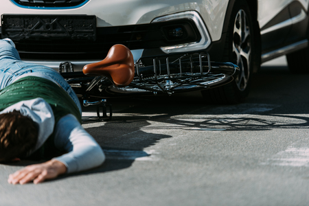 Partial view of male bicycle rider hit by car on road, car accident concept Stok Fotoğraf