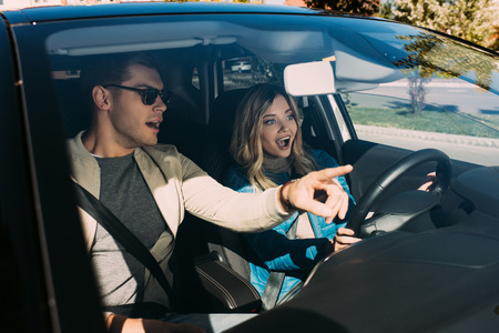 Emotional man pointing way to girlfriend on drivers seat in car