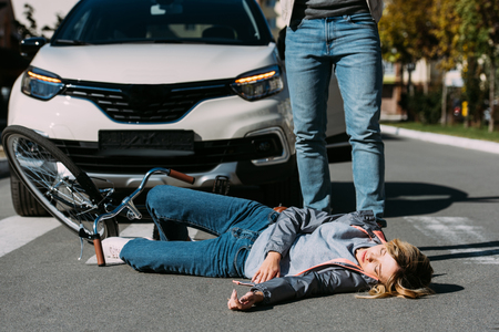 Partial view of young woman mowed down by driver in car on road, car accident concept