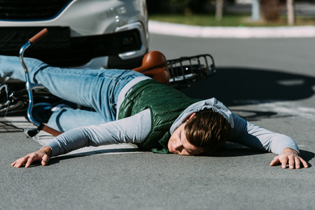 Male bicycle rider hit by car on road, car accident concept 写真素材 - 112271344