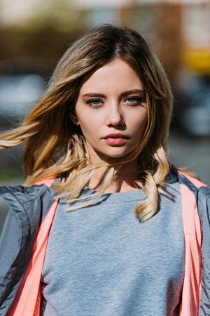 Portrait of beautiful young woman looking at camera on street