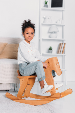 Side view of African american kid sitting on wooden rocking horse
