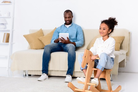 African american father using tablet and daughter sitting on rocking horse Stock Photo