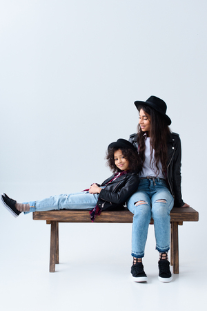 Mother and daughter in similar clothes sitting on bench together isolated on grey