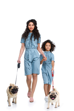 beautiful mother and daughter in similar dresses walking with pugs isolated on white