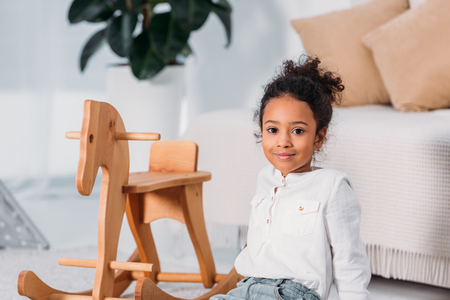 adorable african american kid sitting on floor near rocking horse