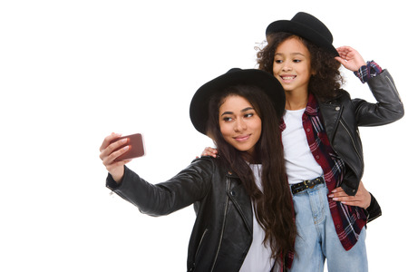 stylish mother and daughter taking selfie with smartphone isolated on white Stock Photo