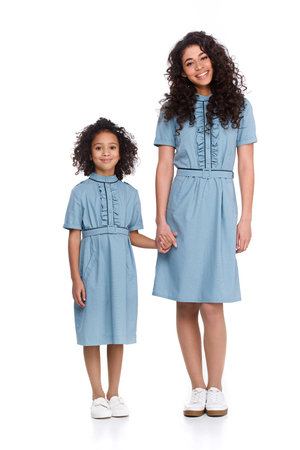 Mother and daughter in similar dresses holding hands isolated on white