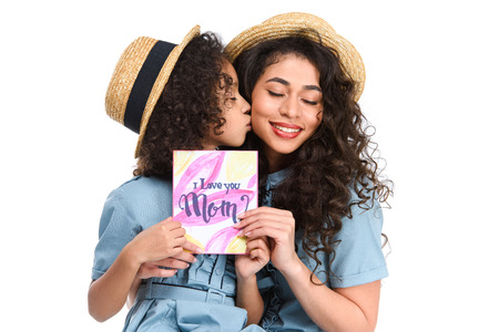Daughter with mothers day greeting card kissing her mother isolated on white