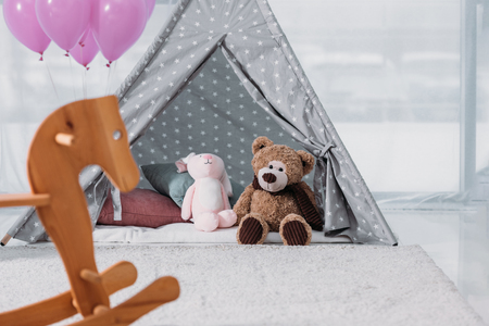 Rocking horse with balloons and soft toys in room Stock Photo