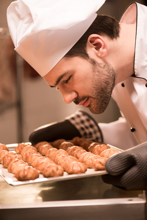 Side view of confectioner looking at eclairs on baking pan in hands