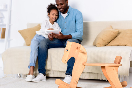 African american father and daughter watching something on tablet with rocking horse on foreground