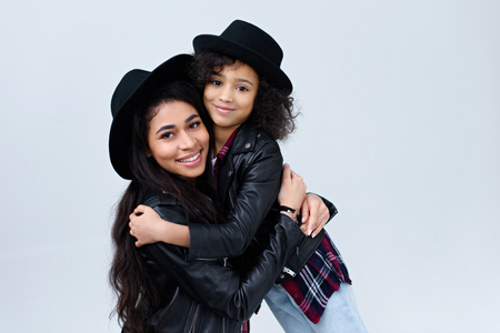 Smiling stylish mother and daughter in similar clothes embracing and looking at camera isolated on grey Reklamní fotografie