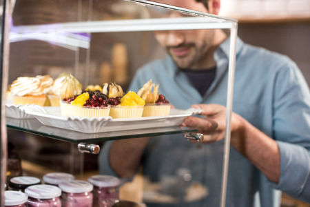 Selective focus of barista taking pastry out box in coffee shop
