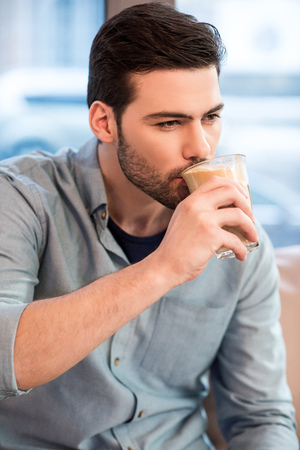 portrait of young handsome man drinking ice coffee in cafe 스톡 콘텐츠