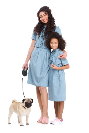 young mother and daughter in similar dresses with pug on leash isolated on white Фото со стока