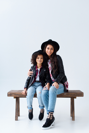 stylish young mother and daughter in similar clothes sitting on bench together isolated on grey Фото со стока - 111696453