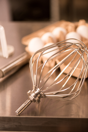 Close up view of whisk and raw eggs for making cream on counter in restaurant