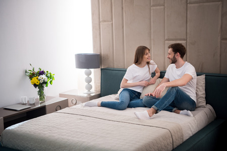 Happy couple sitting on bed in cozy modern bedroom