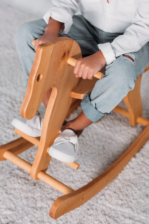 Cropped image of African american kid sitting on rocking horse