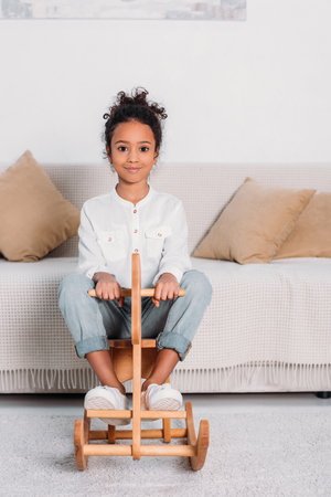 African american kid sitting on wooden rocking horse and looking at camera